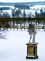 Statue looks onto a snow filled landscape